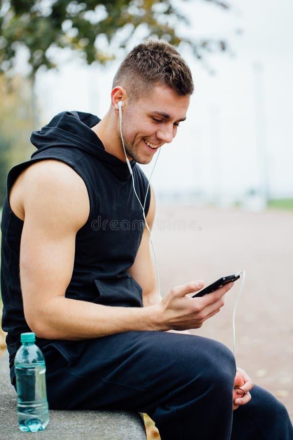 Άτομο ικανότητας που φορά sportswear που ακούει τη συνεδρίαση μουσικής σε έναν πάγκο πετρών Χαλαρώστε μετά από το σκληρό workout, στοκ φωτογραφία