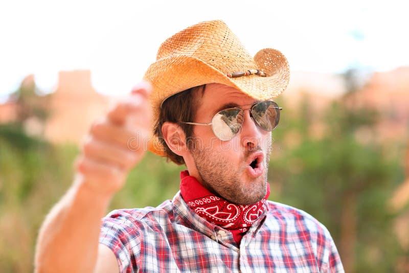 Άτομο κάουμποϋ με τα γυαλιά ηλίου και την υπόδειξη καπέλων στοκ εικόνες