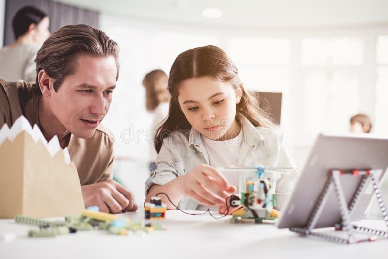 Άτομο και παιδί που εξετάζουν το ρομπότ στοκ φωτογραφία με δικαίωμα ελεύθερης χρήσης