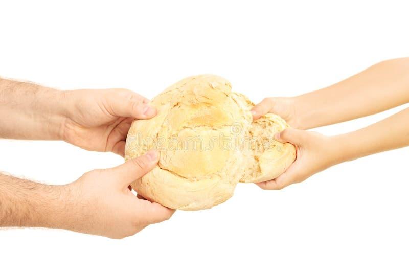 Άτομο και παιδί που σπάζουν χώρια μια φραντζόλα ψωμιού στοκ εικόνες με δικαίωμα ελεύθερης χρήσης