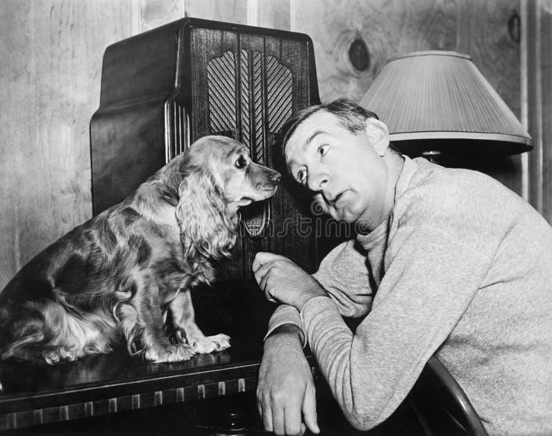 Άτομο και σκυλί που ακούνε το ραδιόφωνο (όλα τα πρόσωπα που απεικονίζονται δεν ζουν περισσότερο και κανένα κτήμα δεν υπάρχει Εξου στοκ εικόνα