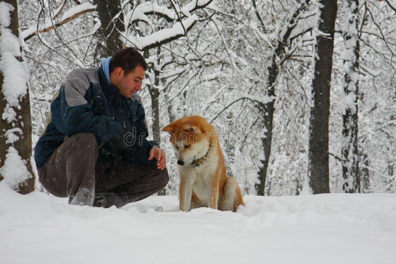 Άτομο και σκυλί στο χιόνι στοκ εικόνες με δικαίωμα ελεύθερης χρήσης