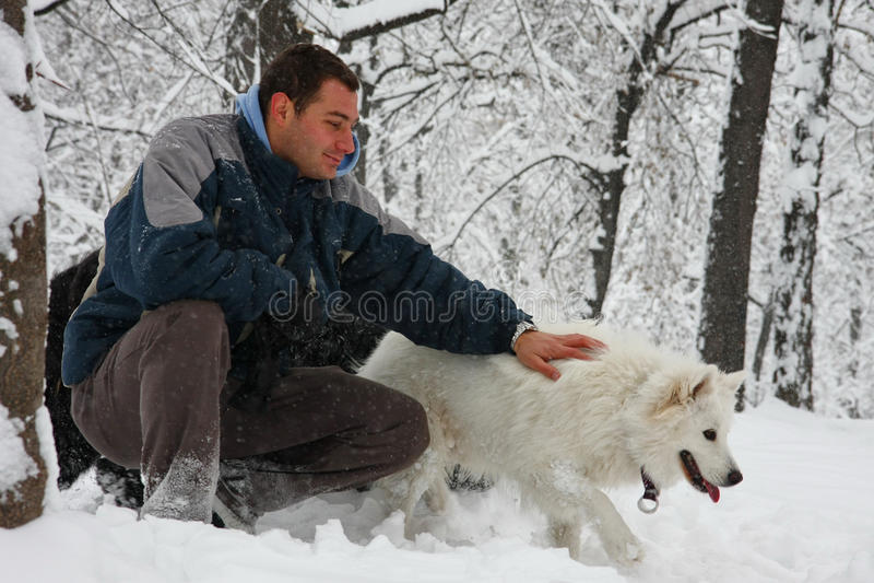 Άτομο και σκυλί στο χιόνι στοκ φωτογραφία