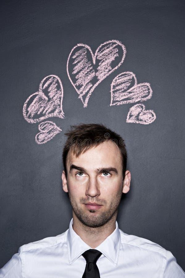 Άτομο και συρμένες κιμωλία καρδιές, τοίχος πινάκων στοκ εικόνες