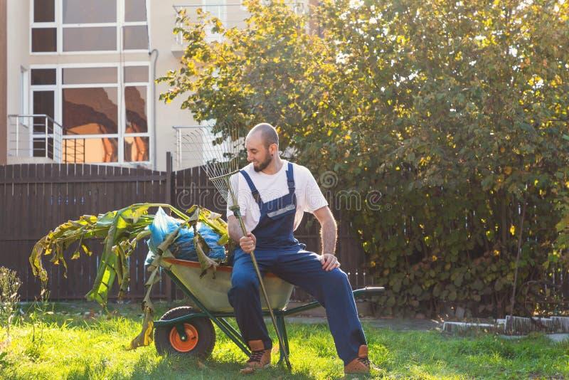 Άτομο-κηπουρός που στηρίζεται μετά από να καθαρίσει το ναυπηγείο Το χαμόγελο και χαλαρώνει μετά από την εργασία Κηπουρική και καθ στοκ φωτογραφίες