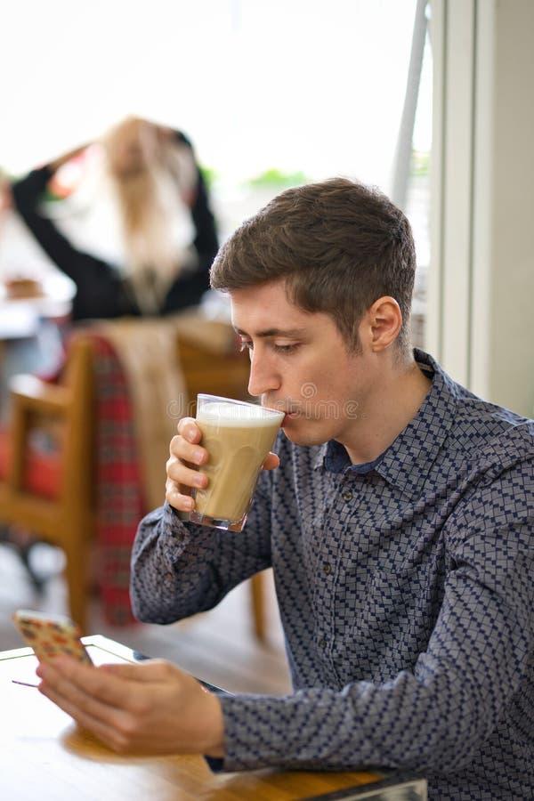 Άτομο κινηματογραφήσεων σε πρώτο πλάνο με τον καφέ και το smartphone στοκ εικόνα με δικαίωμα ελεύθερης χρήσης