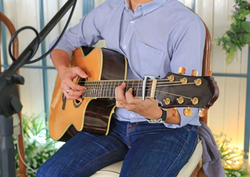 Άτομο κινηματογραφήσεων σε πρώτο πλάνο που παίζει την ακουστική κιθάρα στο κατάστημα καφέδων στοκ φωτογραφίες