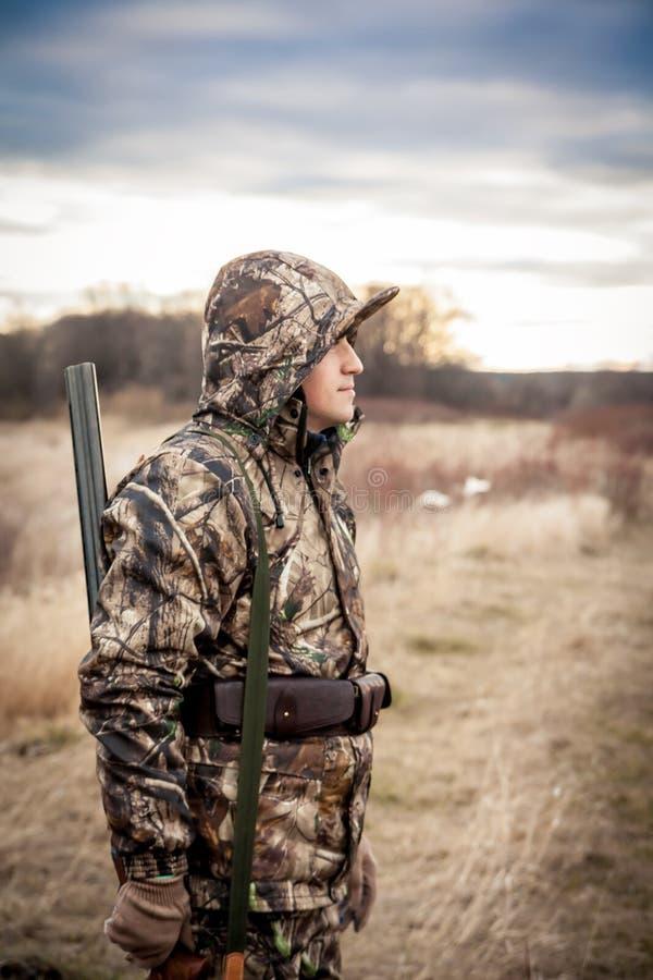 Άτομο κυνηγών με το κυνηγετικό όπλο στην κάλυψη που στέκεται στον αγροτικό τομέα κατά τη διάρκεια του κυνηγιού στοκ φωτογραφίες