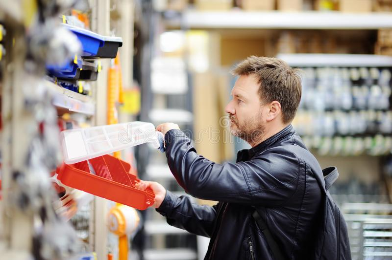 Άτομο Μεσαίωνα που επιλέγει το σωστό κιβώτιο εργαλείων σε ένα κατάστημα υλικού στοκ εικόνα με δικαίωμα ελεύθερης χρήσης