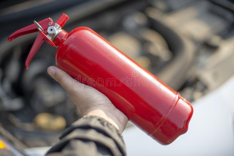 Άτομο με έναν πυροσβεστήρα στο χέρι του κοντά στο αυτοκίνητο στοκ εικόνες