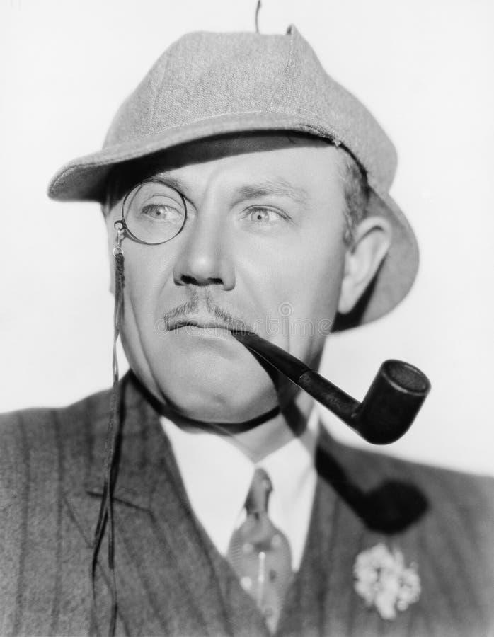 Άτομο με ένα μονόκλ, σωλήνας και ένα καπέλο deerstalker (όλα τα πρόσωπα που απεικονίζονται δεν ζουν περισσότερο και κανένα κτήμα  στοκ φωτογραφία με δικαίωμα ελεύθερης χρήσης