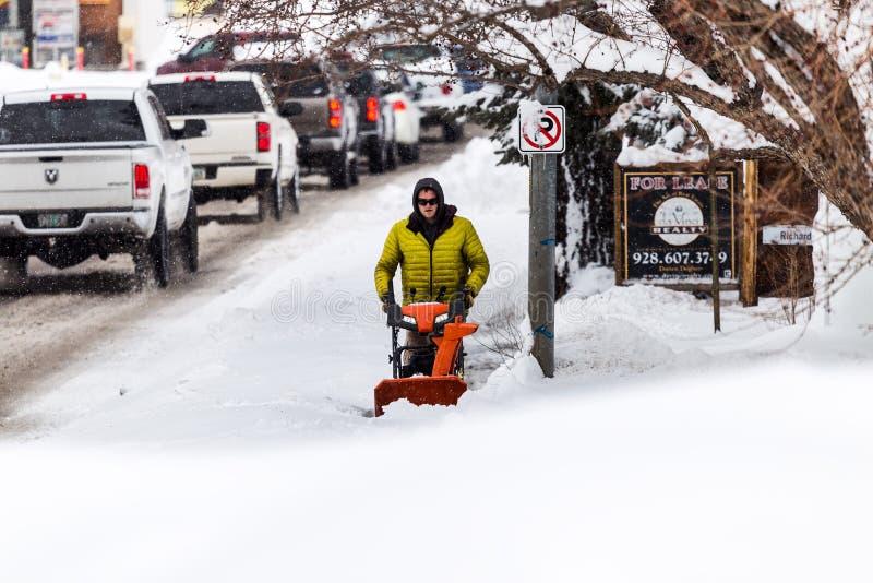 Άτομο με ένα πεζοδρόμιο καθαρίσματος ανεμιστήρων χιονιού στοκ εικόνες