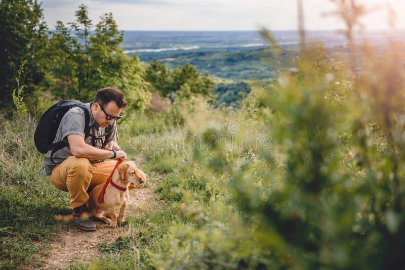 Άτομο με ένα σκυλί που στηρίζεται στο ίχνος πεζοπορίας στοκ φωτογραφία με δικαίωμα ελεύθερης χρήσης