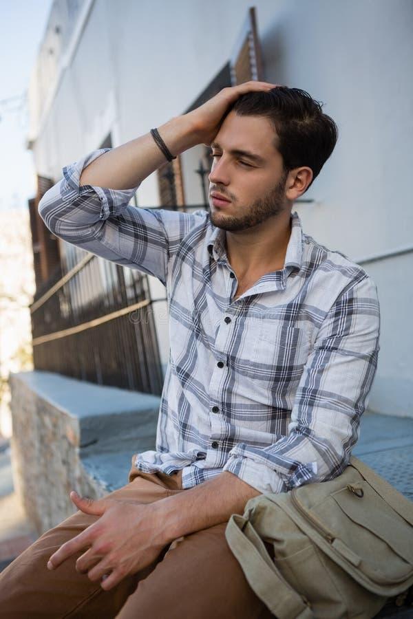 Άτομο με κλειστή τη μάτια συνεδρίαση στο διατηρώντας τοίχο στοκ φωτογραφία