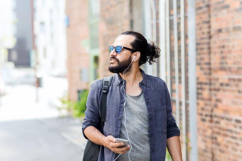 Άτομο με τα ακουστικά και smartphone που περπατά στην πόλη στοκ φωτογραφίες με δικαίωμα ελεύθερης χρήσης