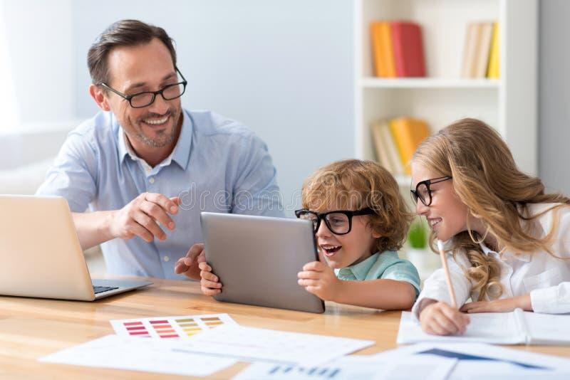 Άτομο με τα παιδιά που εξετάζουν την ταμπλέτα στοκ εικόνες με δικαίωμα ελεύθερης χρήσης