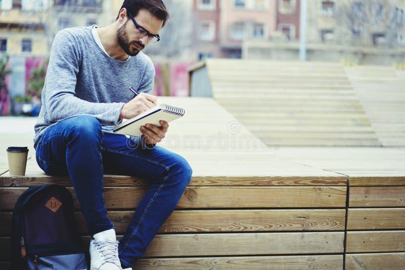 Άτομο με την κινητή τηλεφωνική συνεδρίαση υπαίθρια στην περιοχή πανεπιστημιουπόλεων με το σακίδιο πλάτης και το σημειωματάριο για στοκ φωτογραφία με δικαίωμα ελεύθερης χρήσης