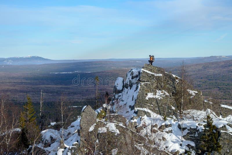 Άτομο με την οδοιπορία σακιδίων πλάτης στα βουνά στο χειμώνα Οδοιπόρος στην κορυφή ο βράχος που καλύπτεται με το χιόνι στοκ εικόνα