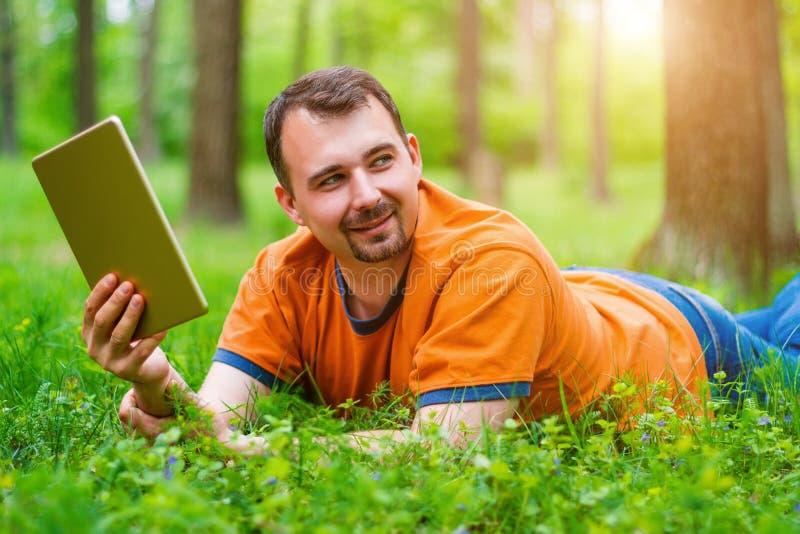Άτομο με την ταμπλέτα στο πάρκο στοκ φωτογραφία