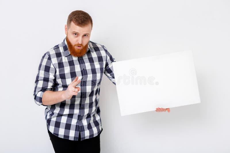 Άτομο με τη γενειάδα που κρατά τη μεγάλη άσπρη κάρτα στοκ εικόνα με δικαίωμα ελεύθερης χρήσης