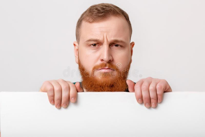 Άτομο με τη γενειάδα που κρατά τη μεγάλη άσπρη κάρτα στοκ φωτογραφίες