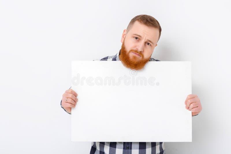 Άτομο με τη γενειάδα που κρατά τη μεγάλη άσπρη κάρτα στοκ εικόνα
