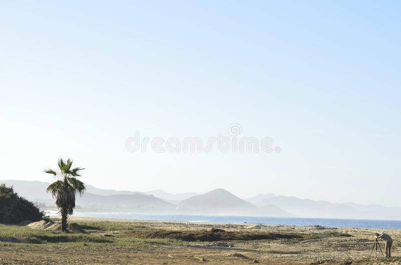 Άτομο με τη κάμερα στο τρίποδο στο τοπίο Baja, Μεξικό ακτών παραλιών στοκ φωτογραφία