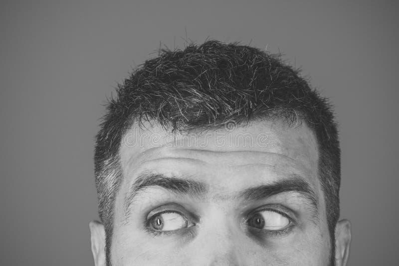 Άτομο με τη σοβαρή συγκίνηση φοβησμένα ή έκπληκτα μάτια του ατόμου στο μπλε υπόβαθρο στοκ εικόνα