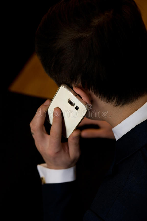 Άτομο με τη συνεδρίαση κινητών τηλεφώνων σε μια επιτραπέζια εργασία στοκ φωτογραφία με δικαίωμα ελεύθερης χρήσης
