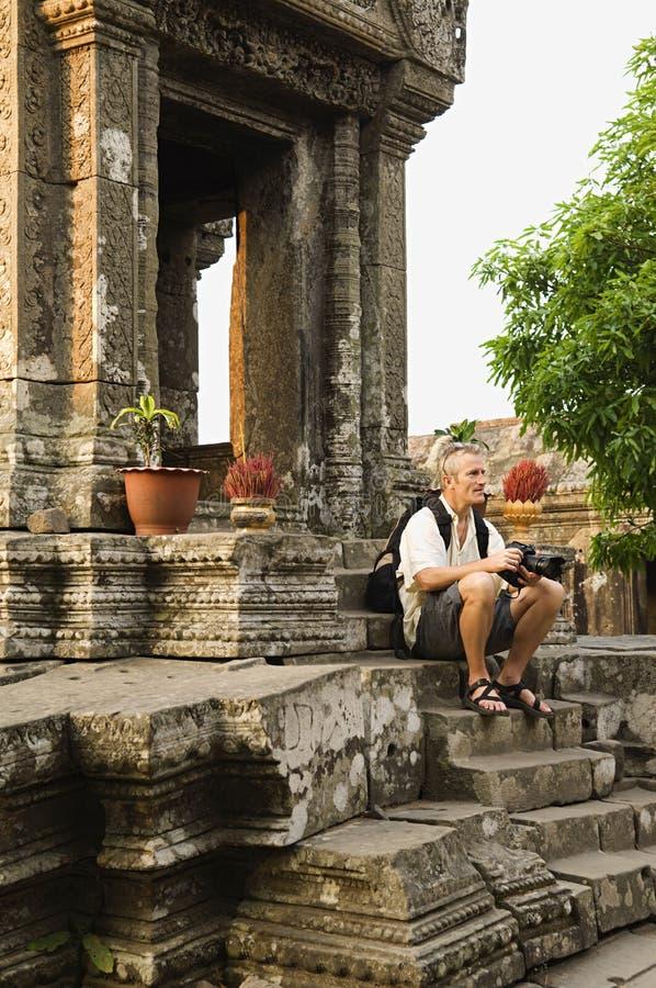 Άτομο με τη συνεδρίαση ψηφιακών κάμερα στα βήματα του αρχαίου ναού στοκ εικόνα