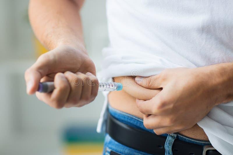 Άτομο με τη σύριγγα που κάνει την έγχυση ινσουλίνης στοκ φωτογραφίες