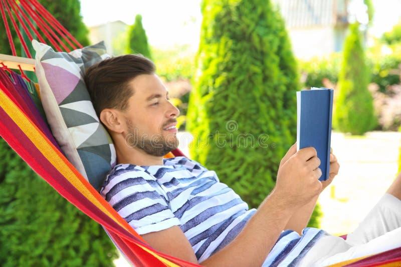 Άτομο με τη χαλάρωση βιβλίων στην αιώρα υπαίθρια τη θερινή ημέρα στοκ φωτογραφία με δικαίωμα ελεύθερης χρήσης