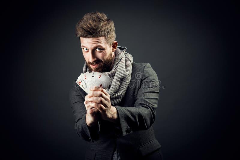 Άτομο με τις κάρτες παιχνιδιού σε ένα σκοτεινό υπόβαθρο στοκ εικόνες