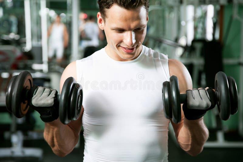 Άτομο με τον εξοπλισμό κατάρτισης βάρους στοκ φωτογραφία