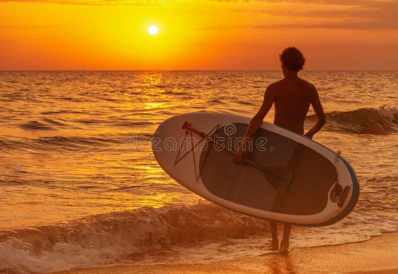 Άτομο με τον πίνακα ΓΟΥΛΙΑΣ που πηγαίνει στη θάλασσα στο ηλιοβασίλεμα στοκ εικόνες
