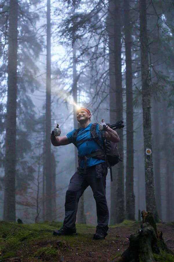 Άτομο με τον προβολέα και σακίδιο πλάτης στο δάσος στοκ φωτογραφία