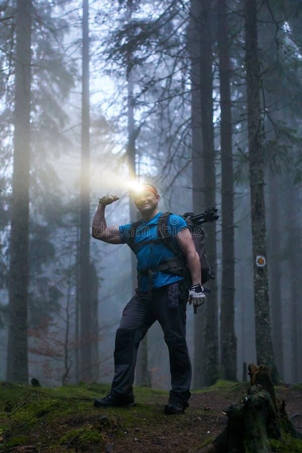 Άτομο με τον προβολέα και σακίδιο πλάτης στο δάσος στοκ φωτογραφίες με δικαίωμα ελεύθερης χρήσης