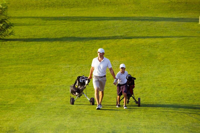 Άτομο με τους παίκτες γκολφ γιων του που περπατούν στο γήπεδο του γκολφ στοκ εικόνες