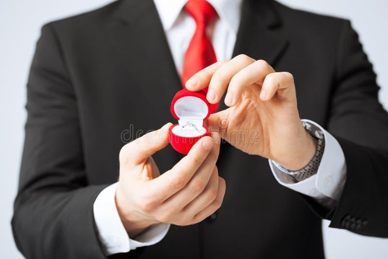 Άτομο με το γαμήλιο δαχτυλίδι και το κιβώτιο δώρων στοκ εικόνα με δικαίωμα ελεύθερης χρήσης