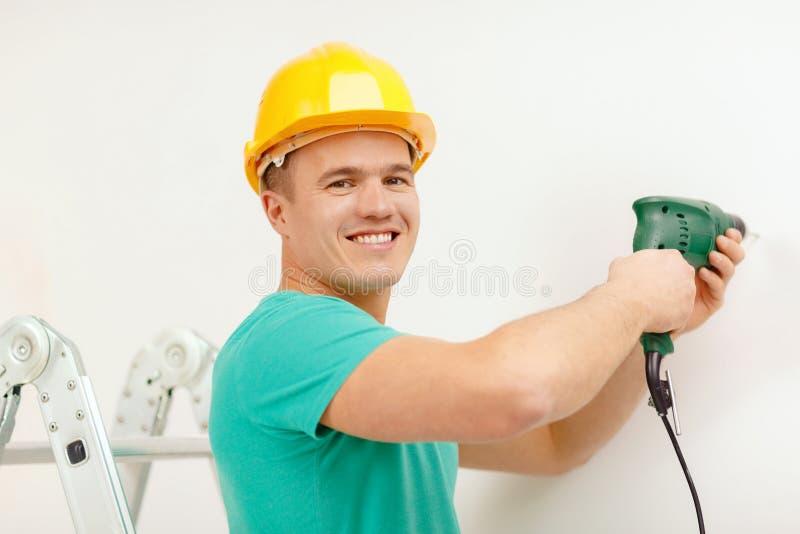 Άτομο με το ηλεκτρικό τρυπάνι που κάνει την τρύπα στον τοίχο στοκ εικόνα
