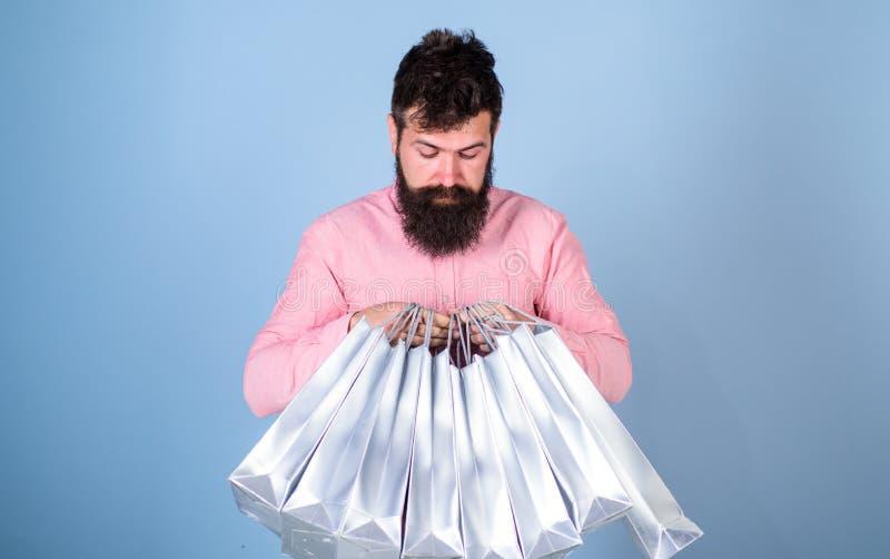 Άτομο με το καθιερώνον τη μόδα hairstyle και γενειάδα που κρατά τις ασημένιες τσάντες Hipster στο ρόδινο πουκάμισο με το περίεργο στοκ φωτογραφίες με δικαίωμα ελεύθερης χρήσης