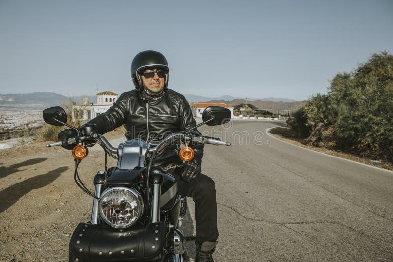 Άτομο με το μαύρα κράνος, το σακάκι και τα γυαλιά ηλίου που στέκονται σε μια κλασική αμερικανική μοτοσικλέτα στοκ εικόνες