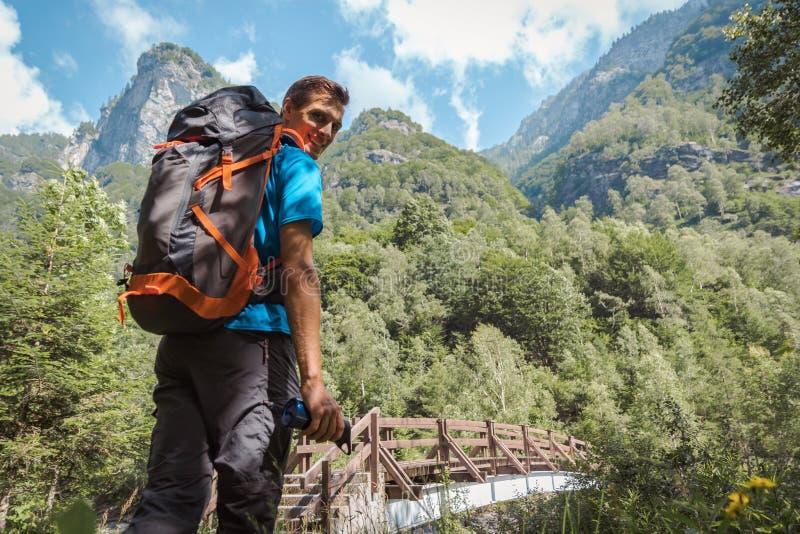 Άτομο με το σακίδιο πλάτης που χαμογελά στη κάμερα που περιβάλλεται από την καταπληκτικά φύση και τα βουνά στοκ φωτογραφίες με δικαίωμα ελεύθερης χρήσης