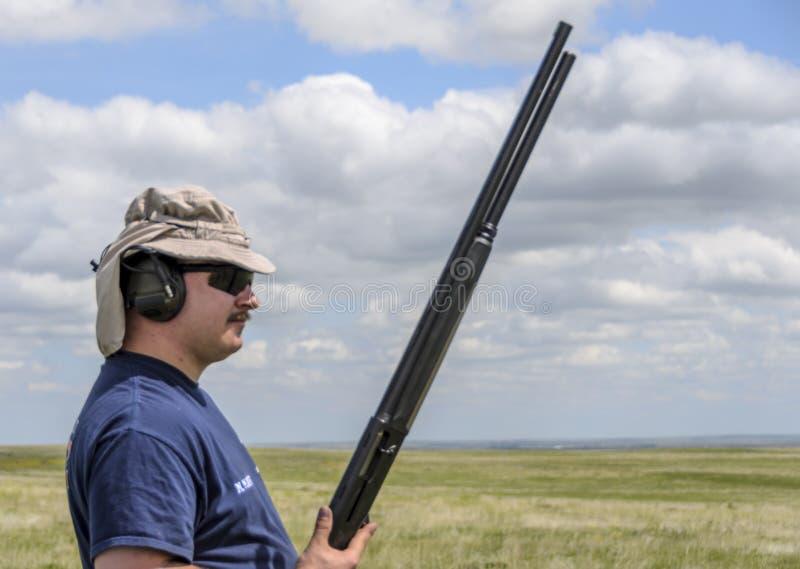 Άτομο με το σκοτεινά καπέλο και το κυνηγετικό όπλο γυαλιών στοκ εικόνες