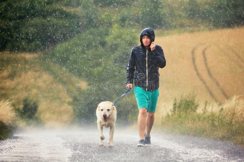 Άτομο με το σκυλί στη δυνατή βροχή στοκ εικόνα με δικαίωμα ελεύθερης χρήσης