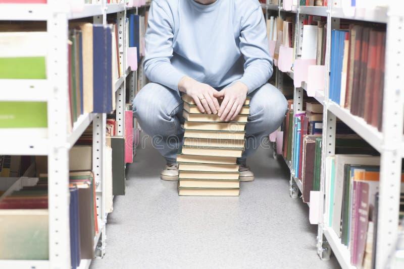 Άτομο με το σωρό των βιβλίων στη βιβλιοθήκη στοκ εικόνες