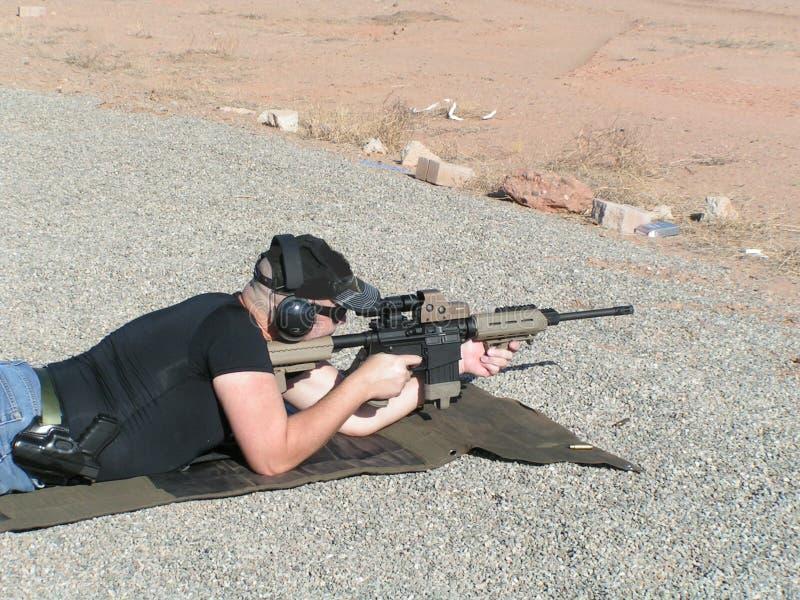 Άτομο με το τουφέκι στη σειρά πυροβολισμού στοκ φωτογραφία με δικαίωμα ελεύθερης χρήσης