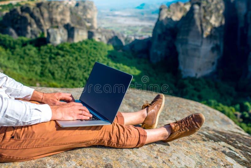 Άτομο με το lap-top στα βουνά στοκ φωτογραφία με δικαίωμα ελεύθερης χρήσης