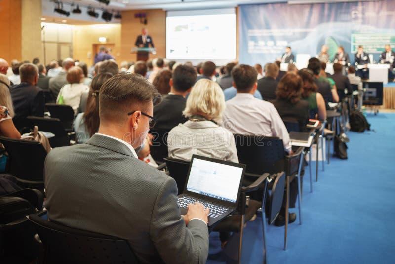 Άτομο με το lap-top στη μεγάλη επιχειρησιακή παρουσίαση στοκ εικόνα με δικαίωμα ελεύθερης χρήσης