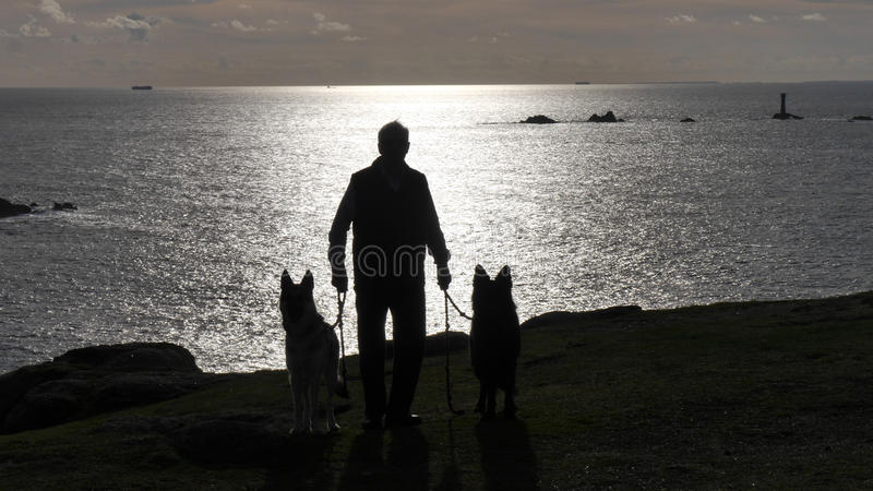 Άτομο με δύο σκυλιά που σκιαγραφούνται στους απότομους βράχους στο φως βραδιού στην Κορνουάλλη UK στοκ εικόνες